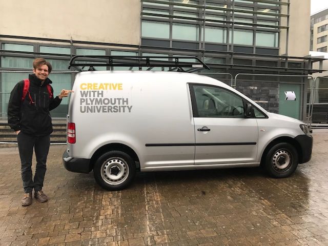 Oliver Broadbent stands next to a van that has the caption on it Creativty with Plymouth Univesity. Oliver is pointing at the word creativity. He was invited to the university to talk about teaching conceptual design